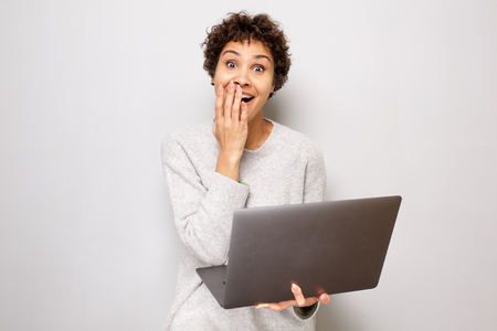 Portrait of surprised young african american woman with laptop computer