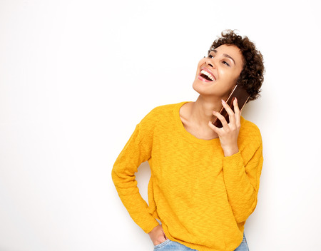 Portrait of happy young woman talking with cellphone by isolated white background