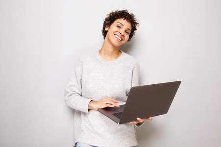 Portrait of beautiful young woman posing by white wall with laptop computer