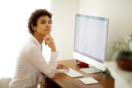 Portrait of young african american woman sitting at desk with computer