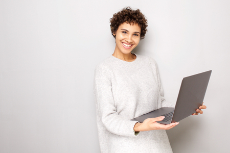 Portrait of smiling young woman holding laptop computer by white background