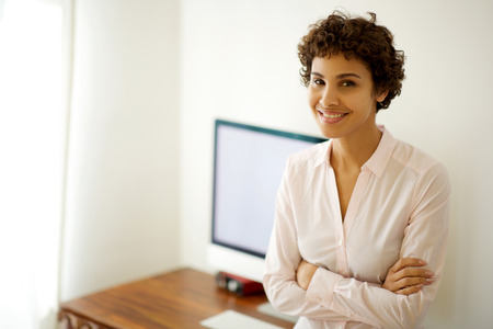 Portrait of businesswoman smiling by computer in office Reklamní fotografie