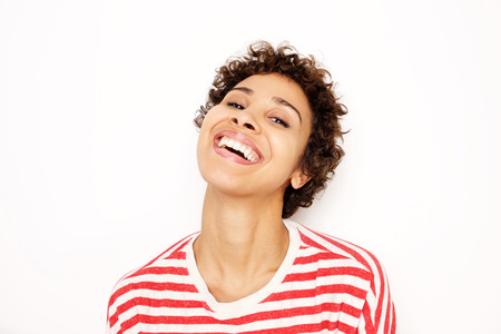 Close up portrait of happy african american woman laughing by white background