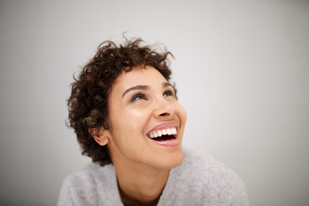 Close up portrait of happy young african american woman laughing and looking up