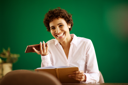 Portrait of happy young woman sitting with book and mobile phone