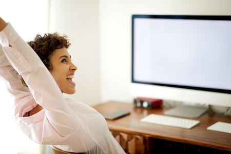 Portrait of happy young woman sitting by computer with arms raised Reklamní fotografie