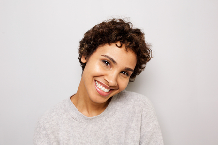 Close up portrait of happy young african american woman smiling white wall Reklamní fotografie