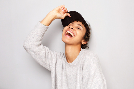 Close up portrait of stylish young woman laughing with cap against white wall