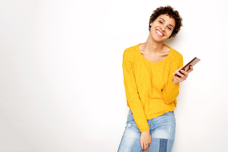 Portrait of happy young woman holding mobile phone by white background