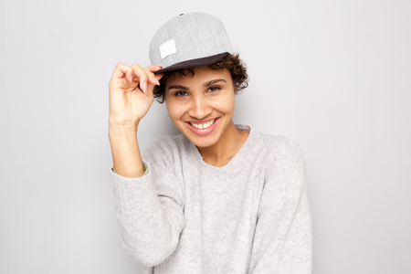 Close up portrait of happy young african american woman smiling with cap by white wall