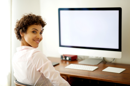 Portrait of young african american woman sitting by computer screen