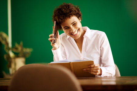 Portrait of beautiful young woman sitting with book and cellphone