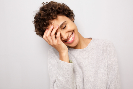 Close up portrait of happy young african american woman laughing with hand by head against white wall