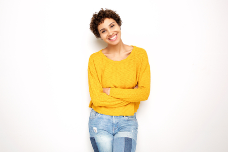 Portrait of happy smiling young woman with arms crossed against isolated white background