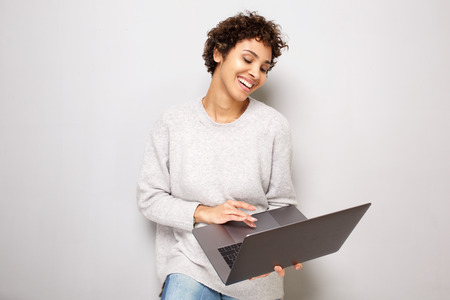 Portrait of happy young african american woman smiling by white background with laptop computer