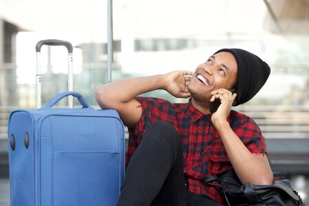 Portrait of happy young black man sitting on floor at station with travel bags and talking with mobile phone Stok Fotoğraf