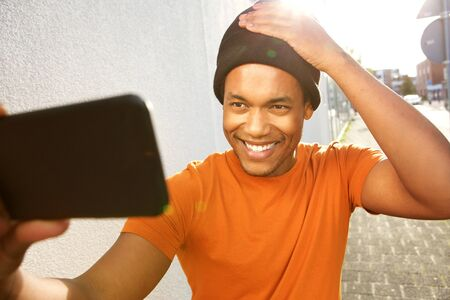 Portrait of handsome young black man taking selfie with mobile phone on street