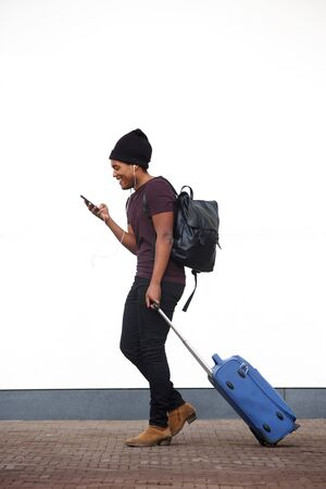 Full body side portrait of african american man walking with luggage and cellphone by white wall