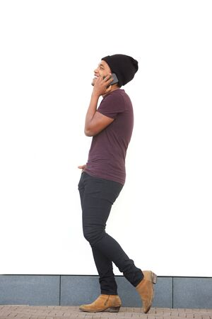 Full body side portrait of african american man walking and talking with cellphone by white wall