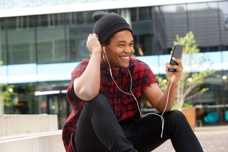 Portrait of happy african american man listening to music with mobile phone and earphones Stock Photo