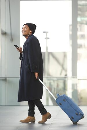 Full length side portrait of happy african american travel man walking at airport with mobile phone and suitcase Stok Fotoğraf