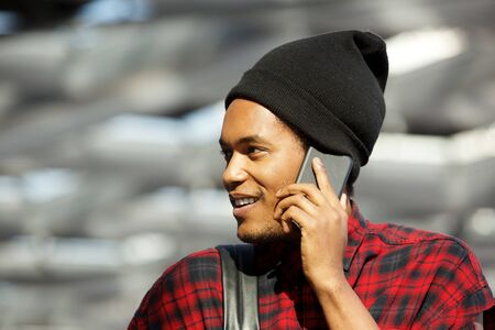 Close up side portrait of african american man with beanie talking on cellphone Stok Fotoğraf