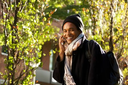 Portrait of happy young african american man walking in city park while talking with cellphone