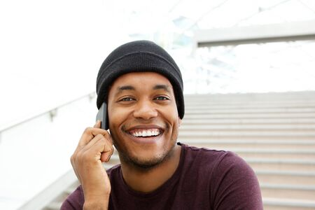 Close up portrait of handsome african american man smiling and talking with mobile phone
