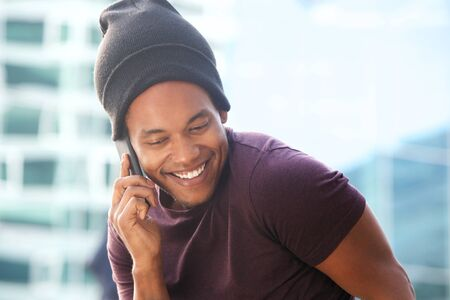 Portrait of happy african american guy talking with cellphone in city
