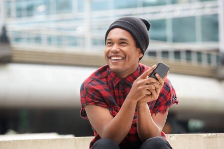 Portrait of happy young black man with beanie sitting outside in city with cellphone and looking away