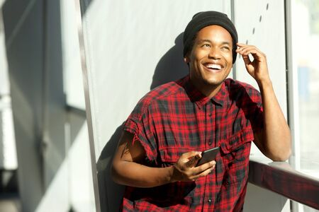 Portrait of fashionable african american man smiling with cellphone