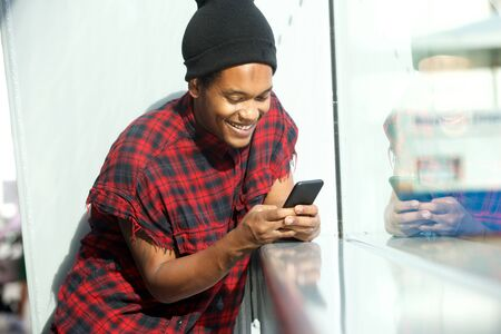 Portrait of smiling african american man looking at mobile phone