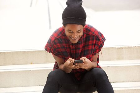 Portrait of young african american man with beanie sitting on steps outside and looking at mobile phone