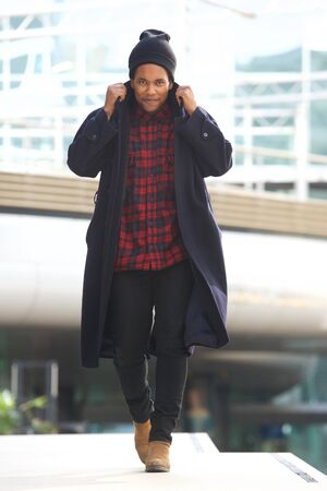 Full body portrait of cool african american walking with winter jacket and beanie in the city
