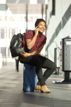 Portrait of happy travel man sitting on suitcase at station while talking on cellphone Stok Fotoğraf
