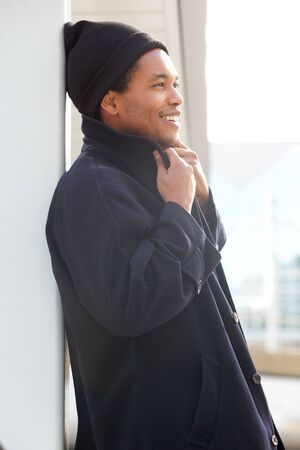 Side portrait of smiling african american man with winter jacket and beanie standing outside
