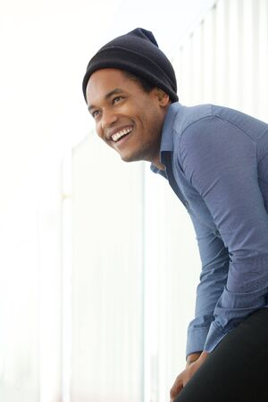 Side portrait of handsome young african american man smiling with beanie