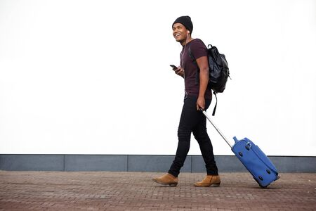 Full body side portrait of african american man walking with suitcase and mobile phone by white wall Stok Fotoğraf