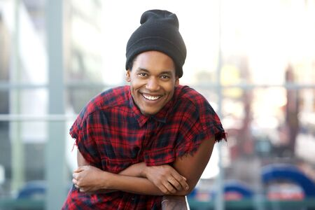 Portrait of cool young black fashion man leaning and smiling
