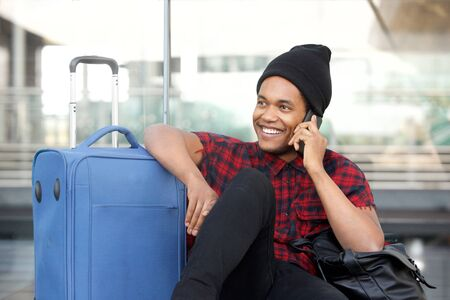 Portrait of happy man sitting on floor at station with travel bags and talking with mobile phone