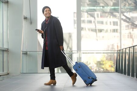 Full length side portrait of smiling travel man walking at airport with cellphone and luggage