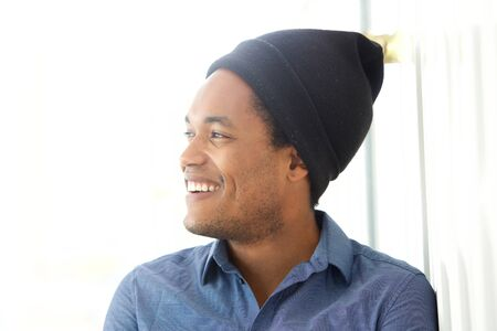 Close up portrait of handsome young african american man smiling and looking away