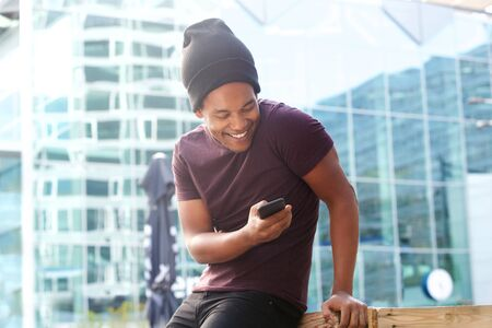 Portrait of cool african american guy looking at mobile phone in city Stok Fotoğraf