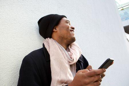 白い背景で携帯電話で笑い、目をそらすハンサムな若いアフリカ系アメリカ人男性の肖像画をクローズアップ