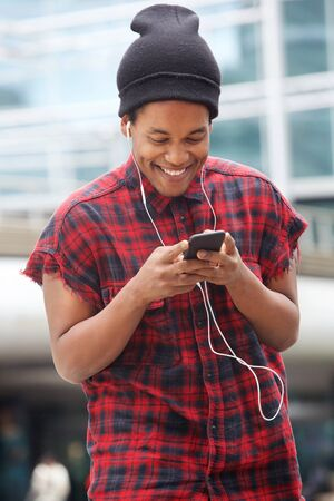 Portrait of smiling african american man listening to music with mobile phone and earphones in the city