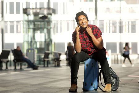 Portrait of happy young black travel man sitting on suitcase while talking on mobile phone in airport