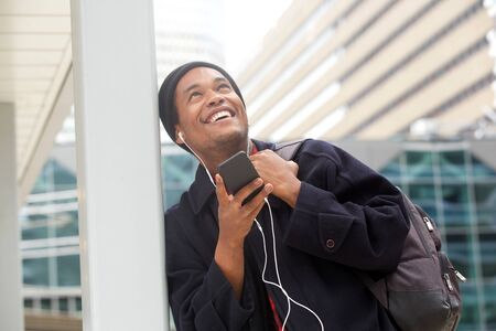 Portrait of happy handsome young black man listening to music with cellphone and looking up in the city