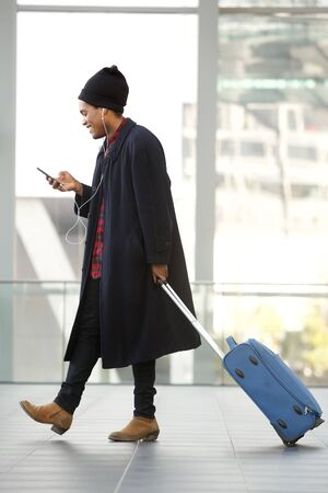 Full length side portrait of african american travel man walking at airport with mobile phone and suitcase