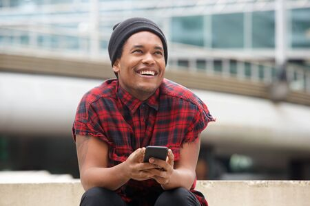 Portrait of happy handsome young black man with cellphone looking away