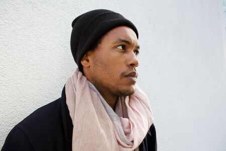 Close up portrait of handsome young african american man with winter jacket, beanie and scarf by white wall Stok Fotoğraf